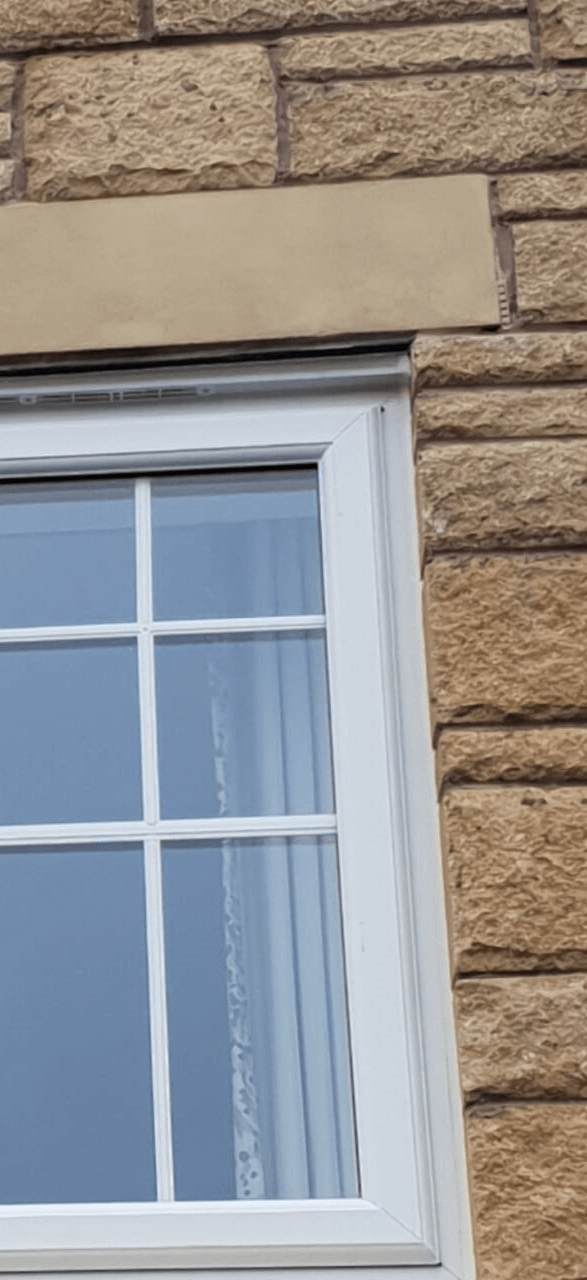 After of repaired damaged stone window.